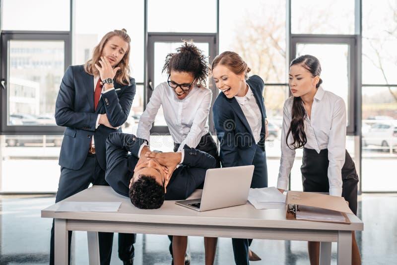 Trzy młodego gniewnego bizneswomanu karze biznesmena lying on the beach na stole fotografia stock