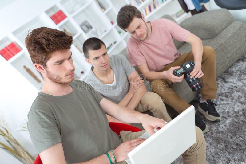 Trzy młodego przyjaciela używa laptop przeglądać ich mknącej sesi obraz royalty free