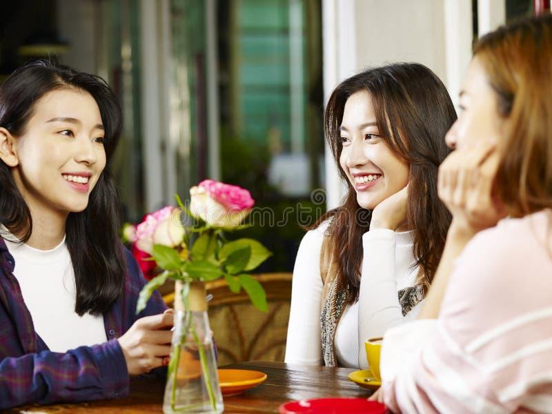 Trzy młodej azjatykciej kobiety gawędzi opowiadać w sklep z kawą zdjęcia stock