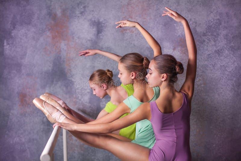 Trzy młodej baleriny rozciąga na barze fotografia royalty free
