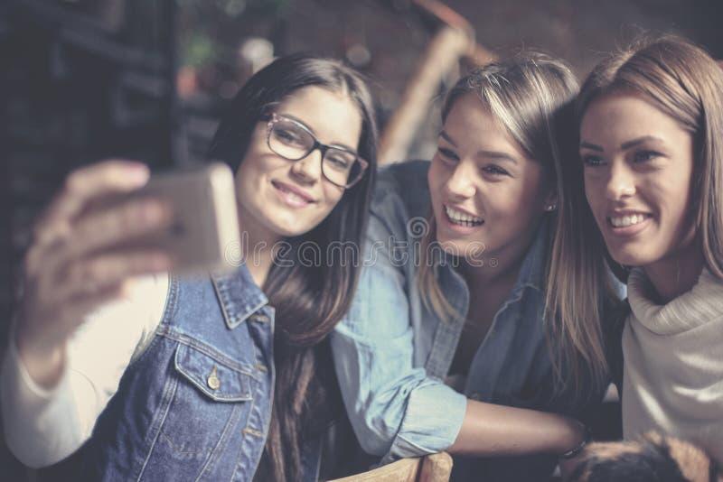 Trzy młodej dziewczyny bierze jaźń obrazek w domu z bliska zdjęcie stock