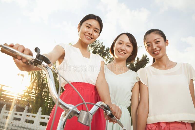 Trzy młodej kobiety z bicyklem zdjęcie stock