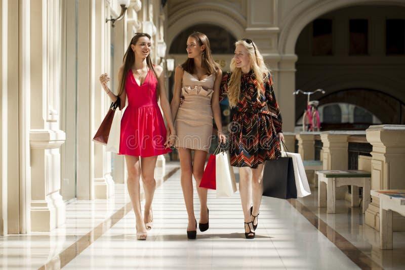Trzy młodej kobiety z niektóre torba na zakupy w centrum handlowym obrazy royalty free