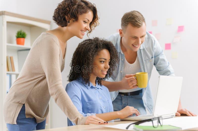 Trzy młodzi ludzie kolaborują w biurze obraz stock