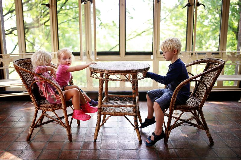 Trzy małego dziecka Siedzi przy Starym bistro stołem w Sunroo fotografia stock