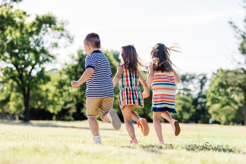 Trzy małego przyjaciela biega wpólnie w parku obraz royalty free