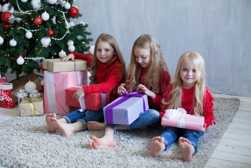 Trzy małej dziewczynki blondynki otwierają Bożenarodzeniowych teraźniejszość choinki nowego roku obraz royalty free