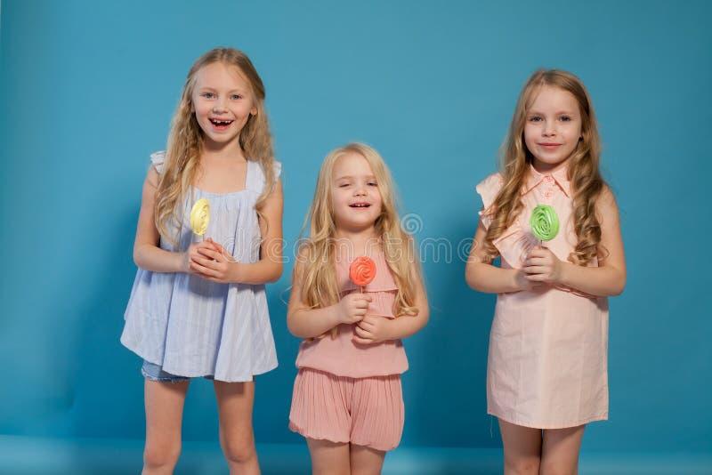 Trzy małej dziewczynki jedzą słodkiego cukierku lizaka zdjęcie royalty free