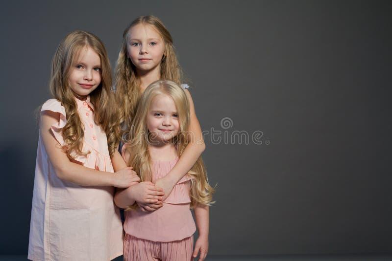 Trzy małych dziewczynek siostr portreta pięknej mody popielaty tło obrazy stock