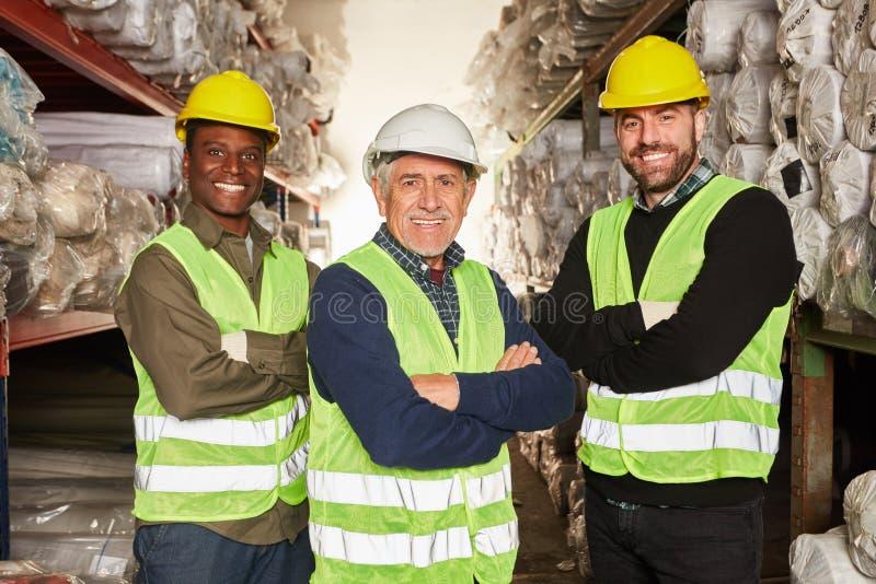 Trzy magazynowego pracownika z krzyżować rękami zdjęcia stock