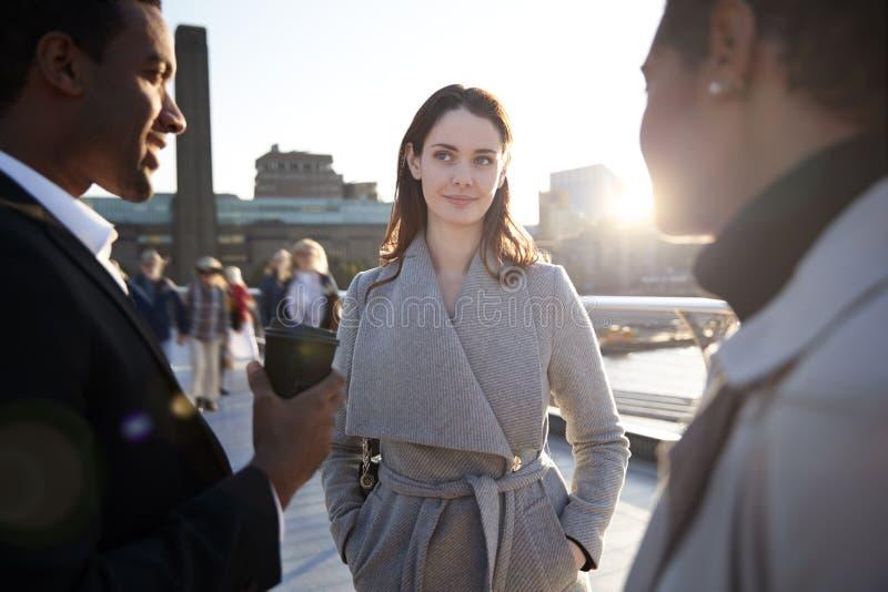 Trzy millennial kolegów statywowy opowiadać na milenium moście jako słońce iść puszek, zakończenie w górę obrazy royalty free