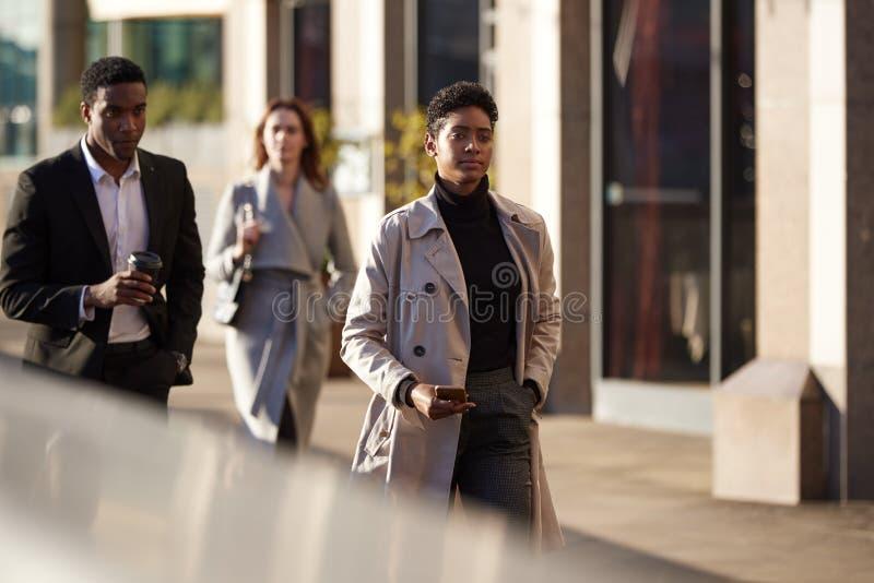 Trzy millennial pracownika citego chodzi w Londyńskiej ulicie, selekcyjna ostrość zdjęcie stock