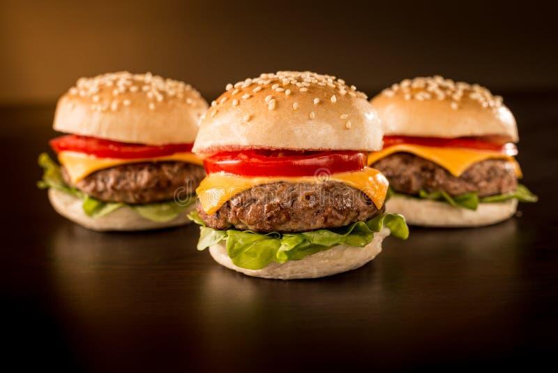 Trzy mini hamburgeru w zmroku nastrojowym obraz stock