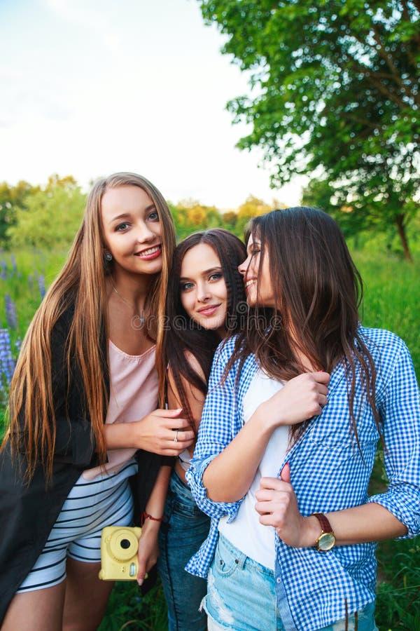 Trzy modniś dziewczyn blondynka i brunetka bierze jaźń portret na polaroid kamerze i ono uśmiecha się plenerowego Dziewczyny ma z zdjęcia stock