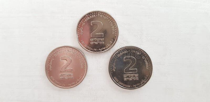 Trzy monety dwa Izraelickiego syklu odizolowywającego na białym tle zdjęcia royalty free