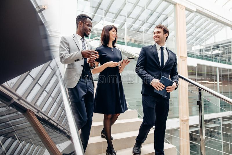 Trzy multiracial ludzie biznesu chodzi w dół na schodkach z cyfrową pastylką fotografia royalty free