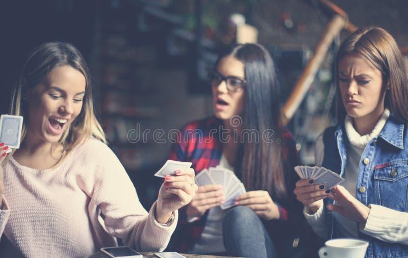 Trzy najlepszego przyjaciela w kawiarni bawić się wpólnie gemowe karty Cl obraz royalty free