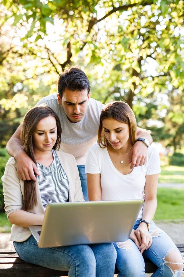 Trzy najlepszego przyjaciela w parku cieszy się i pisać na maszynie na laptopie zdjęcia stock