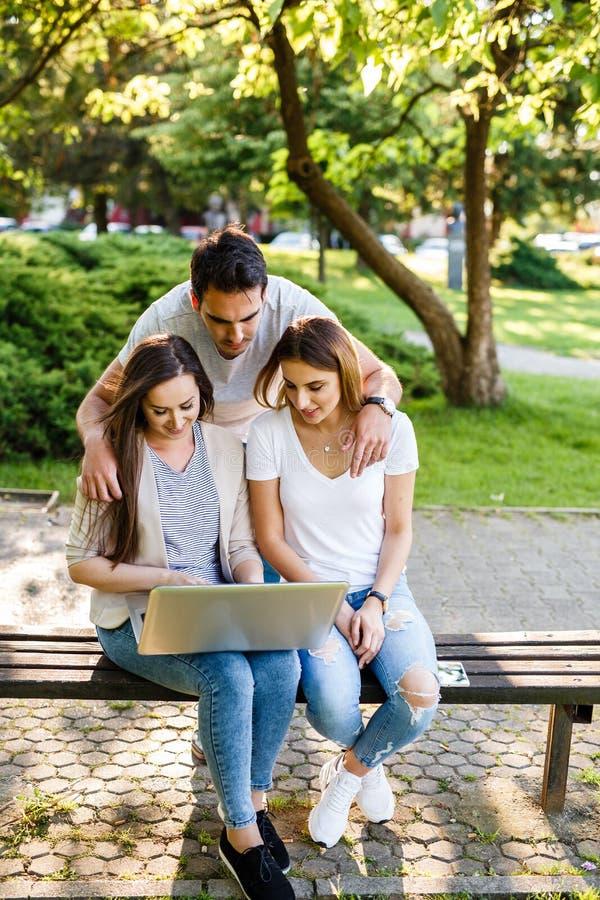 Trzy najlepszego przyjaciela w parku cieszy się i pisać na maszynie na laptopie obrazy stock