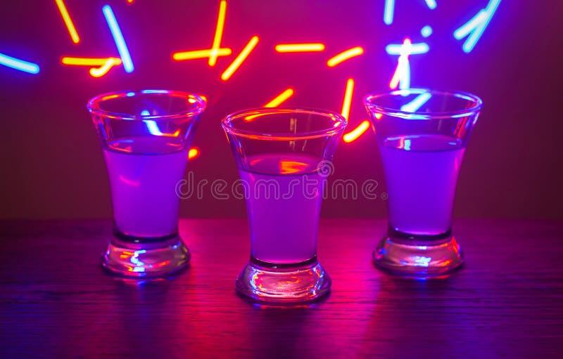 Trzy napoju przy przyjęciem Trzy strzału z koktajlami przy barem Trunek, ajerówka, świeża Błyszczeć na barwionym tle Nocy clu zdjęcia stock