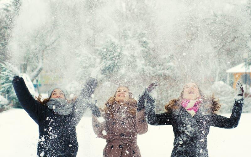 Trzy nastoletniej dziewczyny rzuca śnieg zdjęcie royalty free