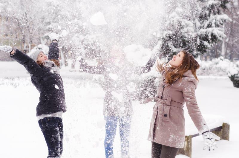 Trzy nastoletniej dziewczyny rzuca śnieg w powietrzu fotografia stock