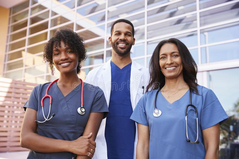 Trzy opieka zdrowotna kolegi stoi na zewnątrz nowożytnego szpitala obraz stock