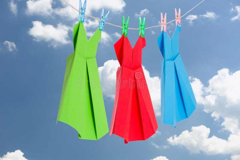 Trzy Origami papieru sukni wiesza na odzieżowej linii przed błękitnym lata niebem (zieleń, czerwień, błękitni) obrazy royalty free