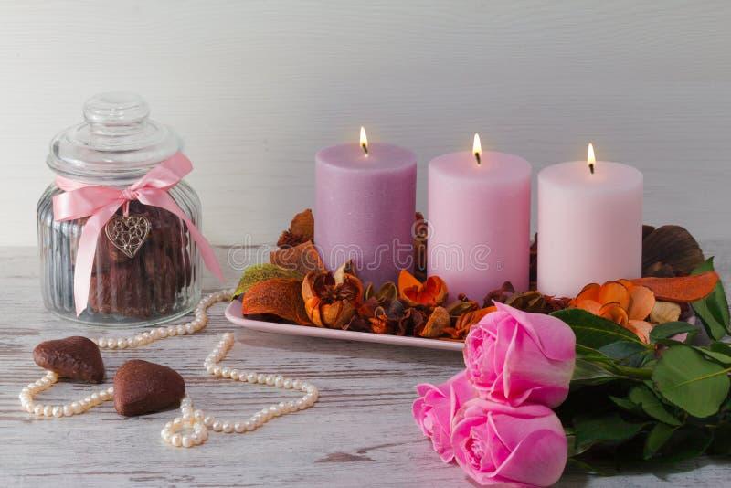 Trzy płonącej świeczki na stojaku z suchymi dekoracyjnymi kwiatami i barkentyną Perełkowa kolia, słój dalej dla ciastek i menchii zdjęcie royalty free