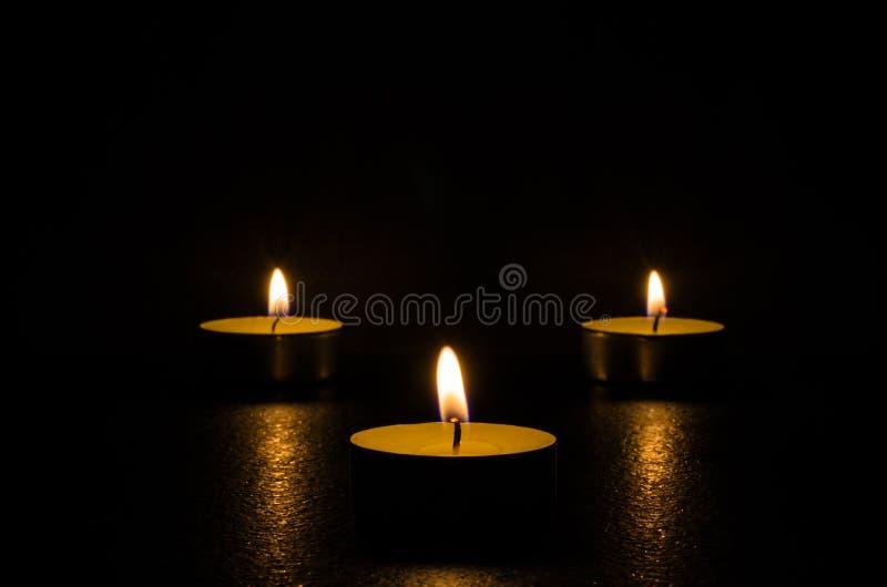 Trzy płonącej świeczki odizolowywającej na czarnym tle obraz stock