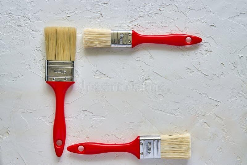 Trzy paintbrushes z czerwonymi rękojeściami na świeżo robić betonowym tle Naprawiania poj?cie Odg?rny widok z kopii przestrzeni? obrazy royalty free