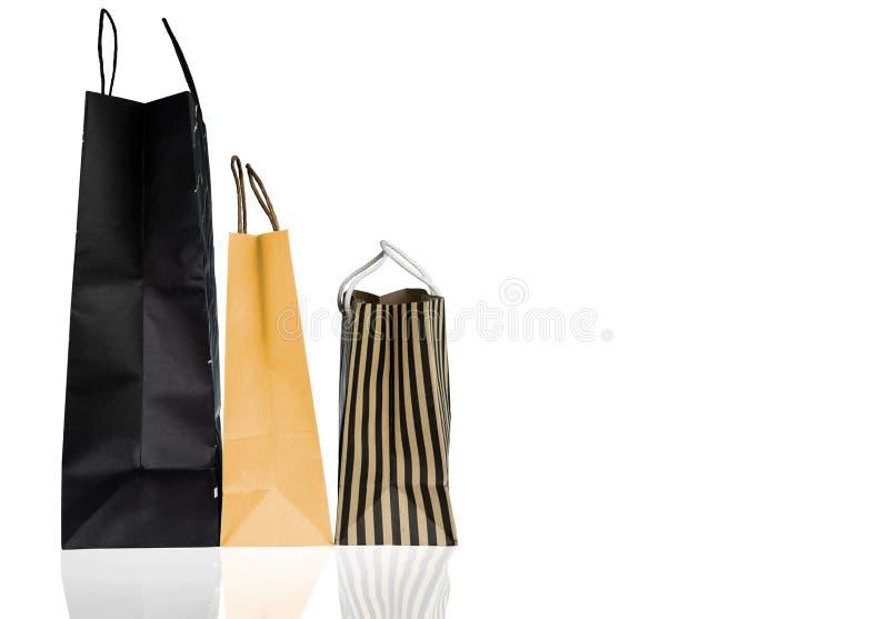 Trzy papierowej torby na zakupy odizolowywającej na białym tle Torba na zakupy z czernią, brązem i żółtym kolorem, Dyskontowy spr obraz stock