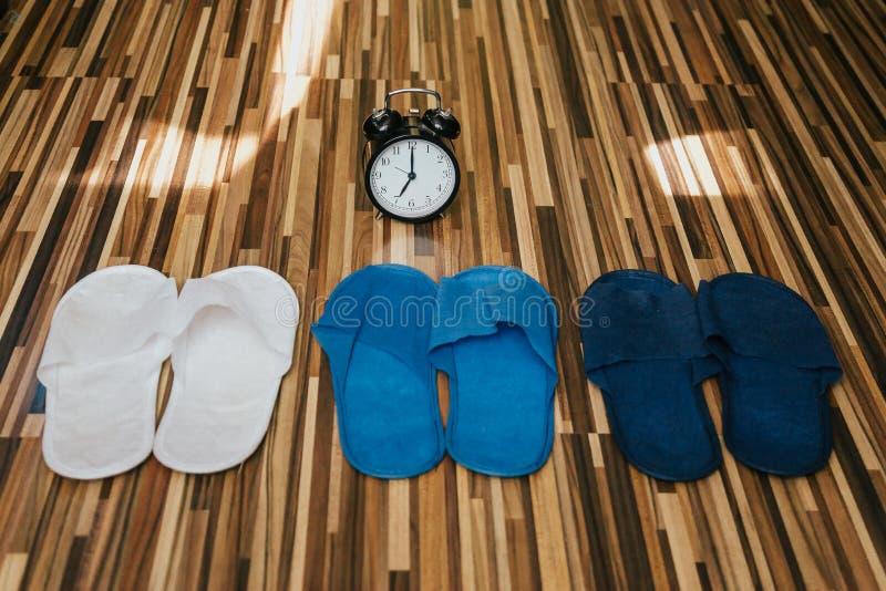 Trzy pary barwioni kapcie i budzik bedtime fotografia royalty free