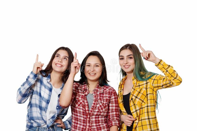 Trzy pięknej młodej dziewczyny wskazują ich palec wskazującego przy one nad ich głowy pojedynczy białe tło Z miejscem fotografia royalty free