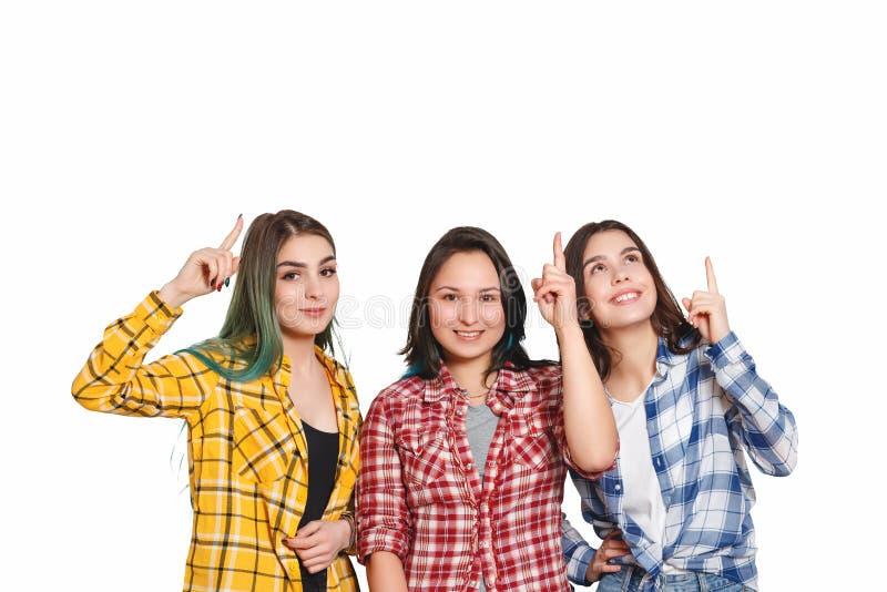 Trzy pięknej młodej dziewczyny wskazują ich palec wskazującego przy one nad ich głowy pojedynczy białe tło Z miejscem fotografia stock