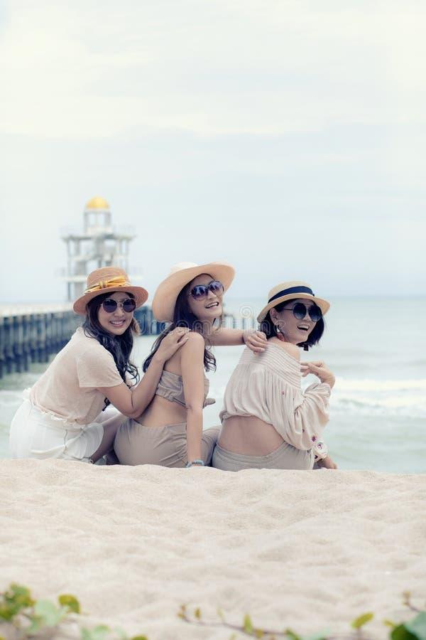 Trzy piękna azjatykcia młoda kobieta śmia się z relaksującą emocją przy urlopową denną stroną zdjęcia stock