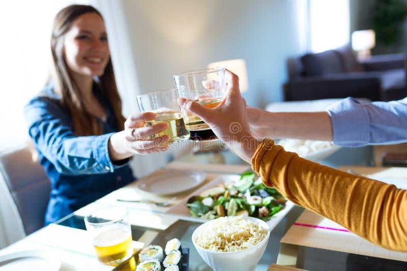 Trzy piękna młoda kobieta wznosi toast z winem podczas gdy jedzący w domu obraz stock