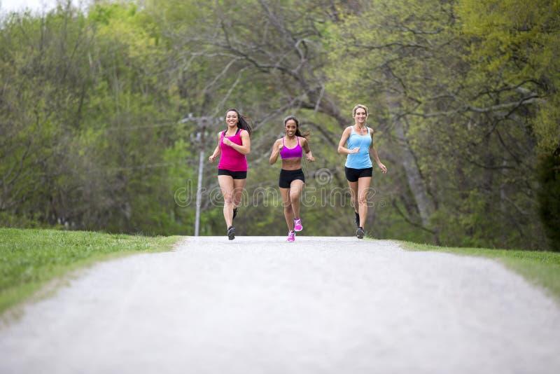 Trzy pięknego kobieta bieg w parku fotografia royalty free