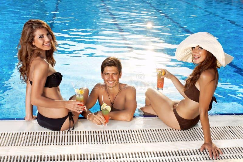 Trzy pięknego ludzie przy basenem zdjęcia stock