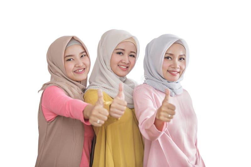 Trzy pięknego rodzeństwa uśmiecha się aprobaty i daje obrazy stock