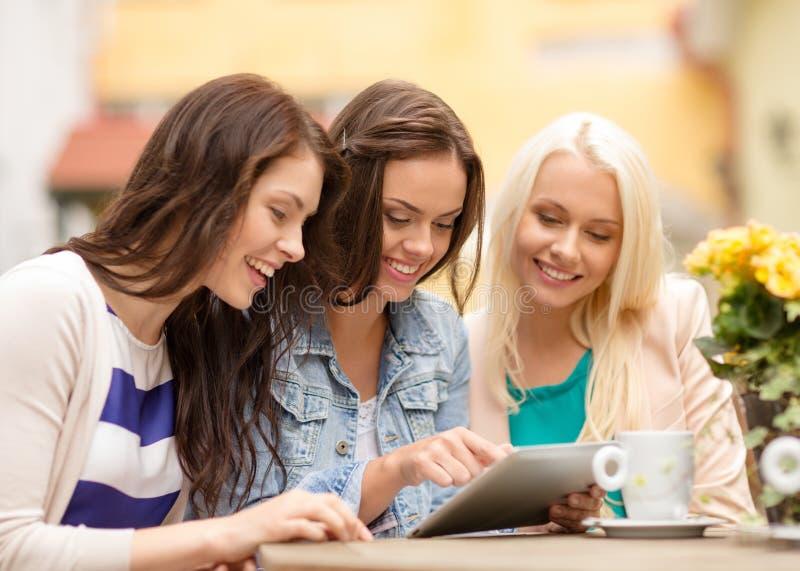 Trzy pięknej dziewczyny patrzeje pastylka komputer osobistego w kawiarni obraz royalty free