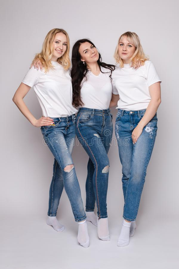 Trzy pięknej kobiety w biały koszula i cajgów pozować obrazy stock