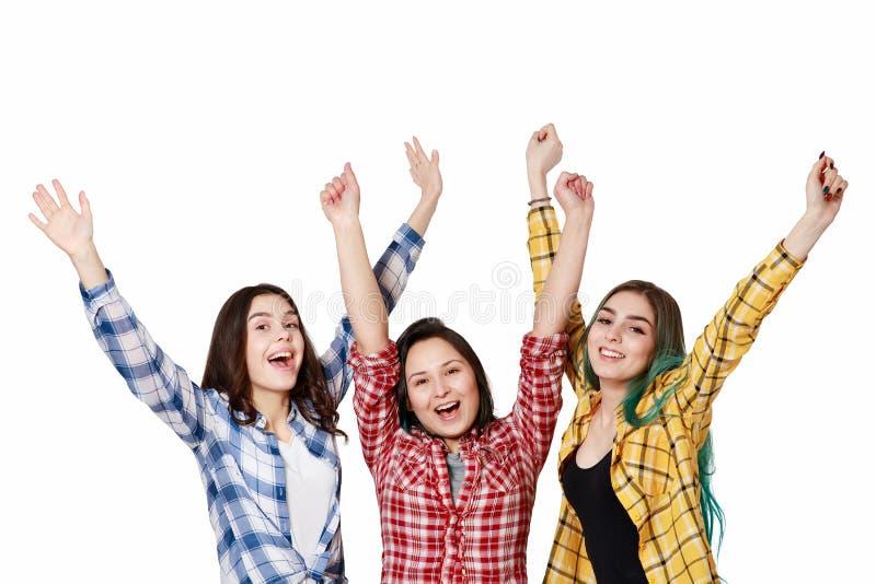 Trzy pięknej młodej dziewczyny z ich rękami w górę szczęśliwie Odizolowywający na białym tle z copyspace zdjęcia stock
