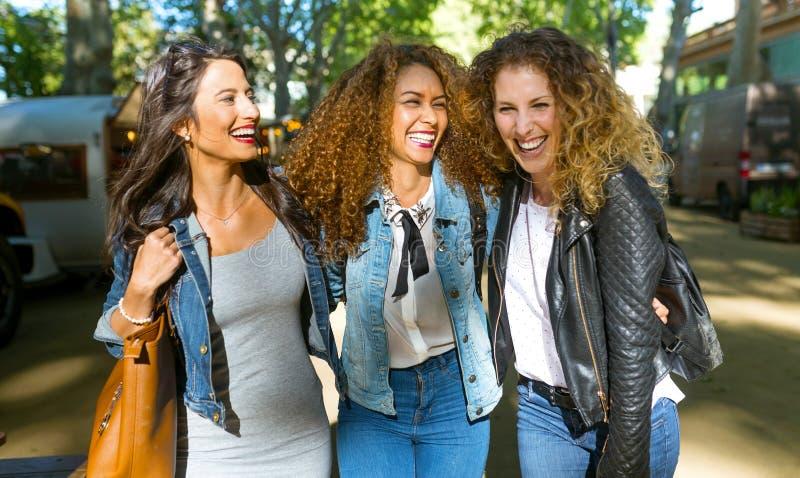 Trzy pięknej młodej kobiety chodzi i opowiada w ulicie zdjęcie stock
