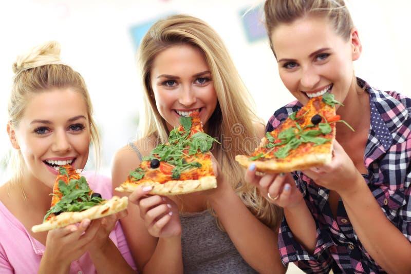 Trzy pięknej młodej kobiety je pizzę w domu fotografia stock