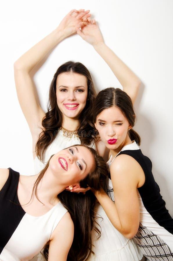 Trzy pięknej modnej dziewczyny ma zabawę odizolowywającą na bielu obrazy stock