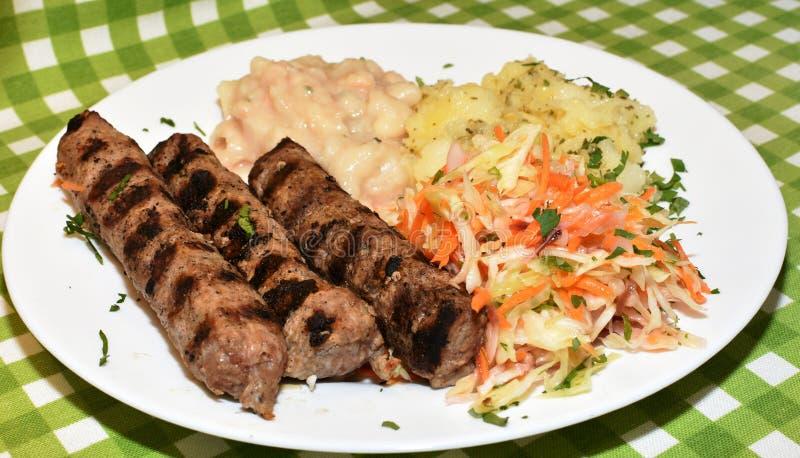 Trzy piec na grillu kebabs z garnirunkiem zdjęcia stock