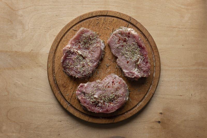Trzy plasterka surowy mięso na round tnącej desce obrazy royalty free