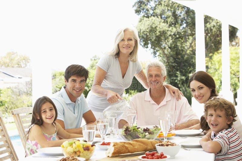 Trzy pokoleń rodzina Cieszy się posiłek Outdoors zdjęcie stock