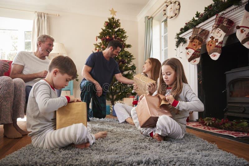 Trzy pokoleń rodzina Jest ubranym piżamy W holu Otwiera prezenty Na święto bożęgo narodzenia W Domu obraz stock